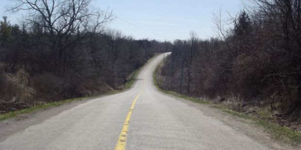 Looking down the middle of a long, country road.