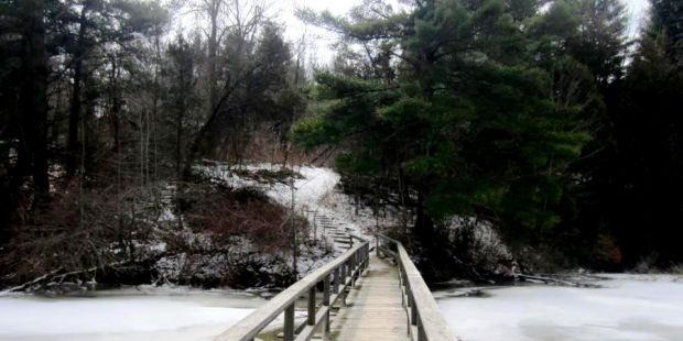 Trail comes to a snow covered bridge and pond.