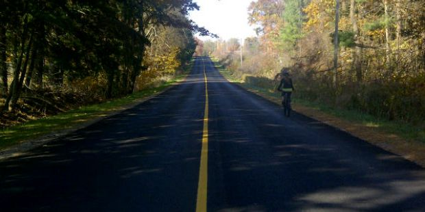 Cyclist on right side of the road in autumn.