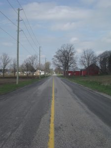 Looking down the centre of a country road with a red barn on the right.