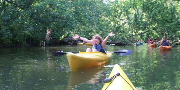 Lady in yellow Kayak with arms up celebrating being on the water. A few kayak friends are behind her.