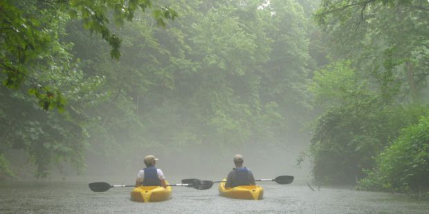 two yellow kayaks floating down a wide misty stream.