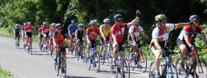 Group of cyclists on the road, waving to those on the sidelines.